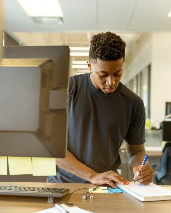 A Hutsy agent taking notes on his notepad while standing in front of a desktop screen